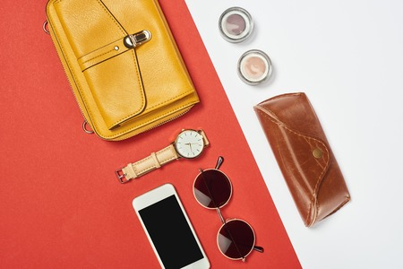 Photo pour Top view of bag, sunglasses, eyeshadow, smartphone, watch and case - image libre de droit