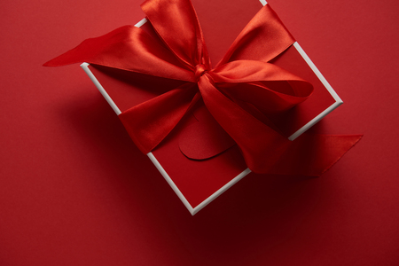 Foto de top view of red gift box with satin ribbon on red background - Imagen libre de derechos