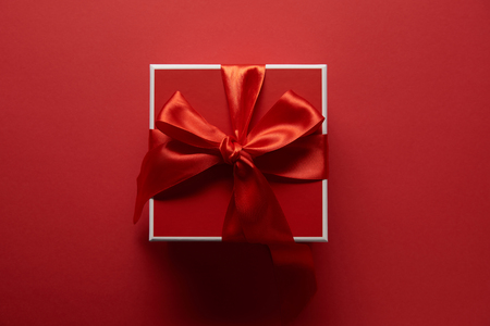 Foto de top view of present with silk ribbon on red background - Imagen libre de derechos