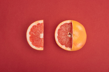 Photo pour top view of grapefruit slice and partially cut grapefruit on red background - image libre de droit