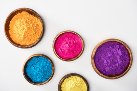 Photo for top view of wooden bowls with pink, blue, yellow, purple and orange holi powder on white background - Royalty Free Image