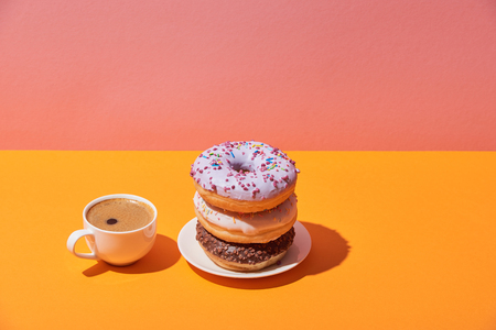 Photo for tasty donuts on saucer and coffe cup on yellow desk and pink background - Royalty Free Image