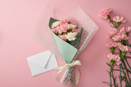 Photo pour beautiful bouquet, pink carnation flowers and white envelope isolated on pink - image libre de droit