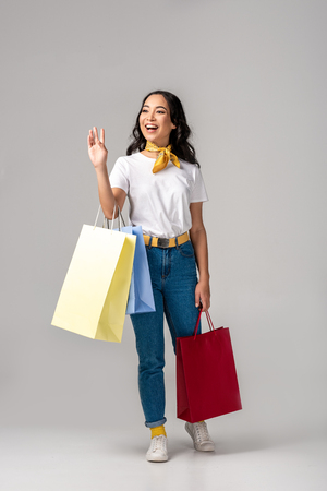 Foto de Trendy dressed young asian woman holding colorful shopping bags and waving by raised hand on grey - Imagen libre de derechos
