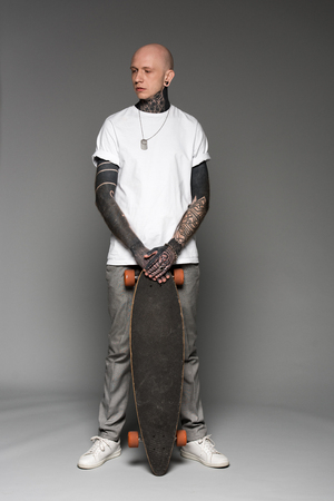 Photo pour full length view of handsome bald tattooed man in white t-shirt standing with skateboard and looking away on grey - image libre de droit