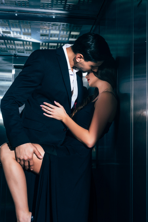 Photo for seductive couple kissing and hugging in elevator - Royalty Free Image