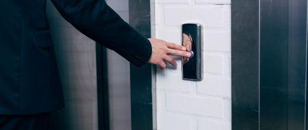 Photo pour cropped view of man pressing elevator button - image libre de droit