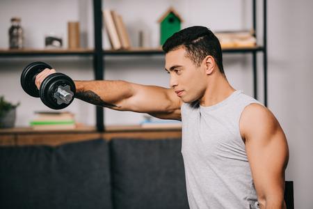Foto de strong mixed race sportsman workout with heavy dumbbell - Imagen libre de derechos