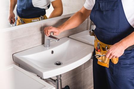 Foto de cropped view of repairman checking faucet after repairing and holding spanner - Imagen libre de derechos
