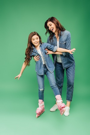 Foto de smiling mother teaching daughter rollerblading on green background - Imagen libre de derechos