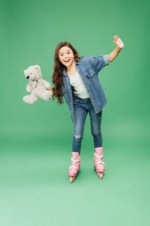 Foto de child rollerblading with outstretched hands and teddy bear on green background - Imagen libre de derechos