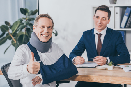 Photo pour businessman sitting at table wile worker in neck brace and arm bandage showing thumb up in office, compensation concept - image libre de droit