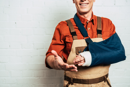Photo for cropped view of repairman with arm bandage standing on white textured background - Royalty Free Image