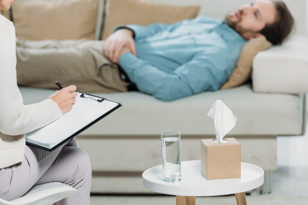 Foto de cropped shot of psychotherapist writing on clipboard while bearded man lying in couch - Imagen libre de derechos