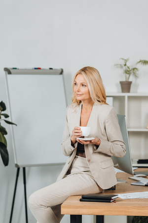 Foto de beautiful smiling businesswoman holding cup of coffee and sitting on table in office - Imagen libre de derechos