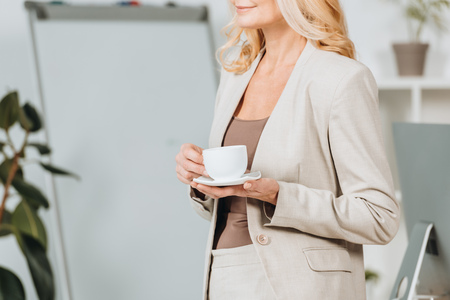 Foto de cropped shot of smiling businesswoman holding cup of coffee in office - Imagen libre de derechos