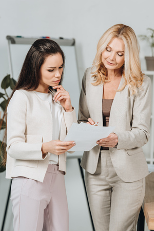 Foto de smiling mature businesswoman pointing at papers and discussing work with young female colleague in office - Imagen libre de derechos