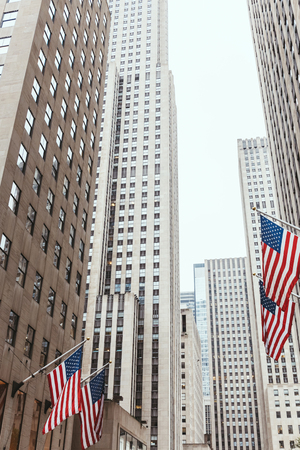 Photo pour low angle view of skyscrapers and american flags on new york city street, usa - image libre de droit