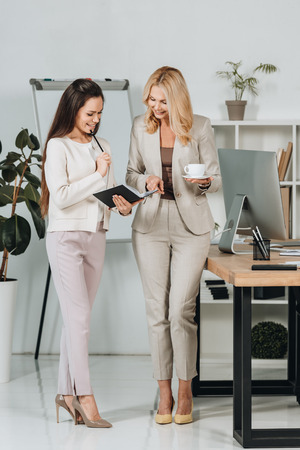 Foto de beautiful happy businesswomen with cup of coffee and notebook standing together and discussing work in office - Imagen libre de derechos