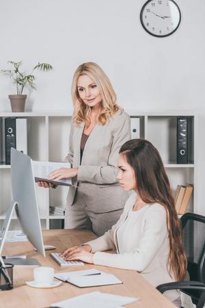 Foto de mature business mentor with folder and young businesswoman looking at desktop computer in office - Imagen libre de derechos