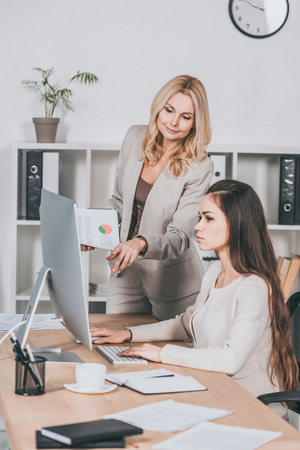 Foto de young businesswoman using desktop computer and mature female mentor pointing at screen - Imagen libre de derechos