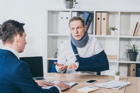 Photo pour middle aged worker in neck brace with broken arm sitting at table and talking to businessman in blue jacket in office, compensation concept - image libre de droit