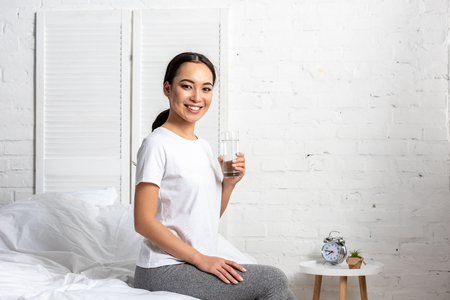 Foto de Beautiful smiling asian girl in white t-shirt sitting on bed with glass of water - Imagen libre de derechos
