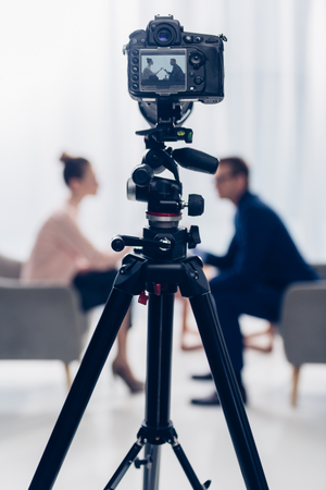 Photo for side view of businessman giving interview to journalist in office, camera on tripod on foreground - Royalty Free Image