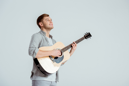 Photo for smiling man in grey clothing playing acoustic guitar isolated on grey - Royalty Free Image