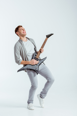Photo for excited man in grey clothing playing electric guitar on grey background - Royalty Free Image