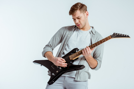 Photo pour handsome focused man in grey clothing playing electric guitar isolated on grey - image libre de droit