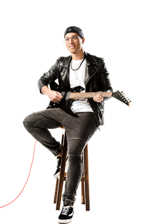 Photo pour smiling male rock musician in leather jacket playing on electric guitar while sitting on chair isolated on white - image libre de droit