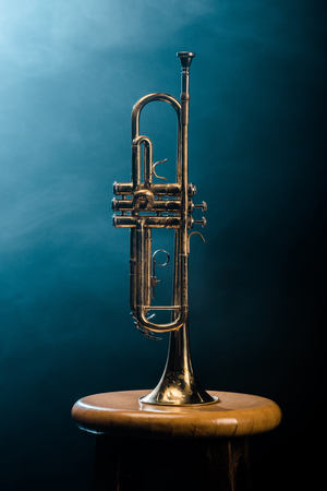 Photo for studio shot of trumpet on chair with dramatic lighting background - Royalty Free Image