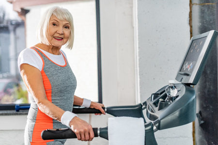 Foto per selective focus of smiling senior sportswoman running on treadmill at sports hall - Immagine Royalty Free