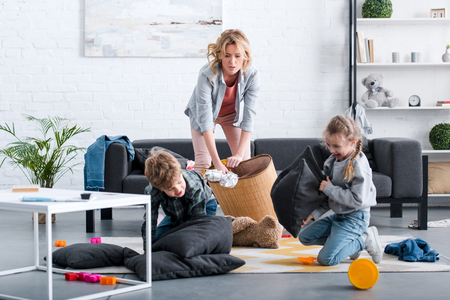 Photo pour emotional tired mother putting toys in basket while naughty kids fighting with pillows - image libre de droit