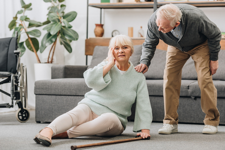 Photo pour senior wife sitting on floor with headache near supportive retired husband - image libre de droit