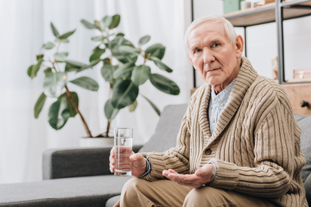 Foto de senior man holding pills and glass of water and looking at camera - Imagen libre de derechos