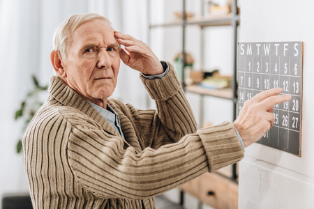 Foto de senior man touching wall calendar and head while looking at camera - Imagen libre de derechos