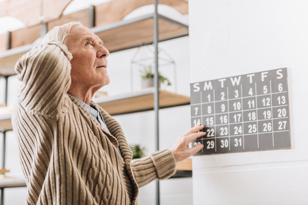 Foto de senior man touching wall calendar and head - Imagen libre de derechos