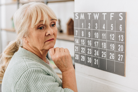 Foto de upset senior woman touching wall calendar and remembering dates - Imagen libre de derechos