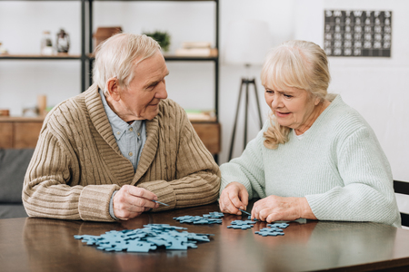 Foto de happy retired couple playing with puzzles at home - Imagen libre de derechos