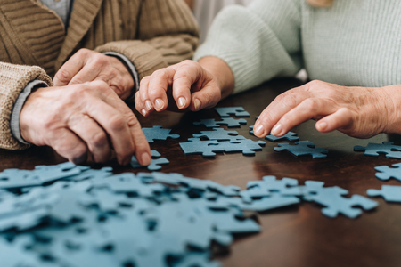 Photo pour cropped view of retired couple playing with puzzles at home - image libre de droit