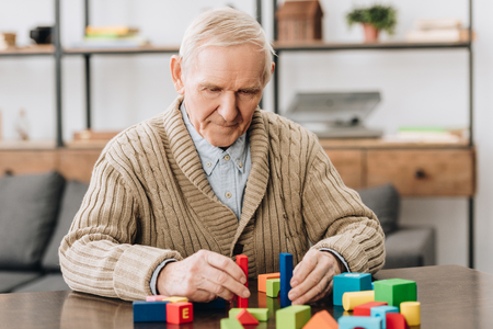 Foto de senior man playing with wooden toys at home - Imagen libre de derechos