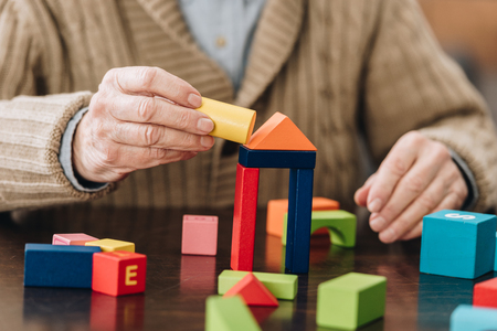 Foto de cropped view of senior man playing with wooden toys on table - Imagen libre de derechos