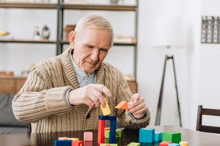 Foto de retired man playing with wooden toys at home - Imagen libre de derechos