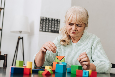 Foto de blonde retired woman playing with wooden toys at home - Imagen libre de derechos