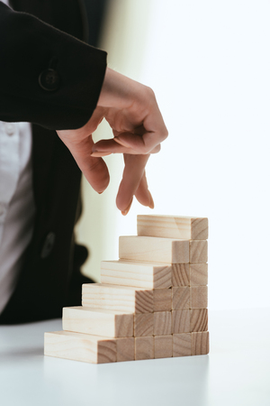 Foto de partial view of woman walking with fingers on wooden blocks symbolizing career ladder - Imagen libre de derechos