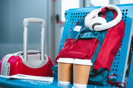 Photo for headphones on backpack near paper cups and baggage in airport - Royalty Free Image