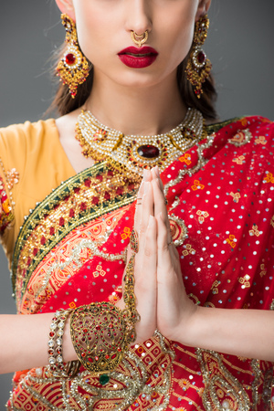 Foto per cropped view of indian woman in traditional clothing with namaste mudra, isolated on grey - Immagine Royalty Free
