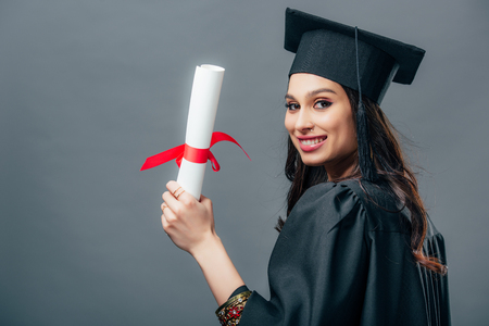 Foto de smiling female indian student in academic gown and graduation cap holding diploma, isolated on grey - Imagen libre de derechos